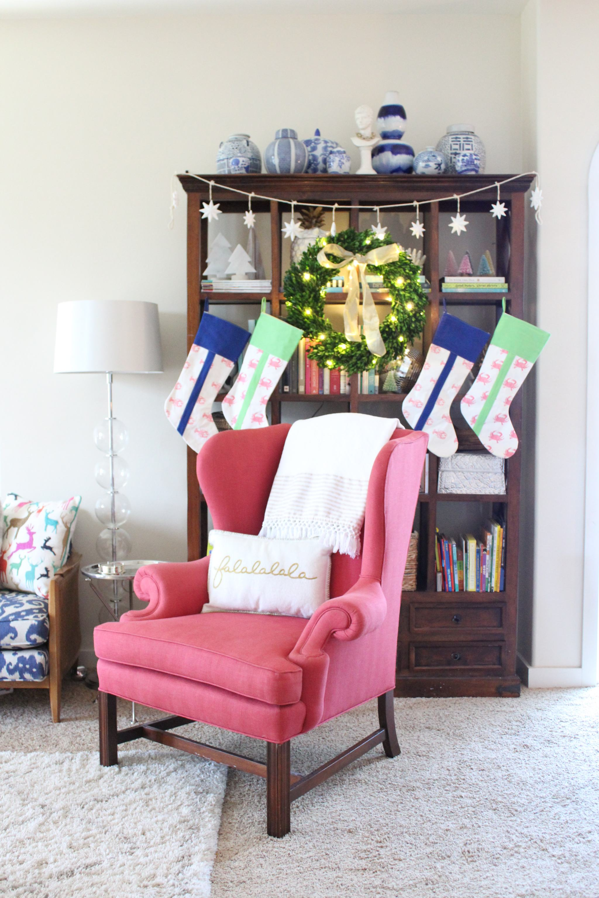 pink chippendale chair - crab and cleek stockings - tall bookcase - blue and white ginger jars - coastal Christmas decor