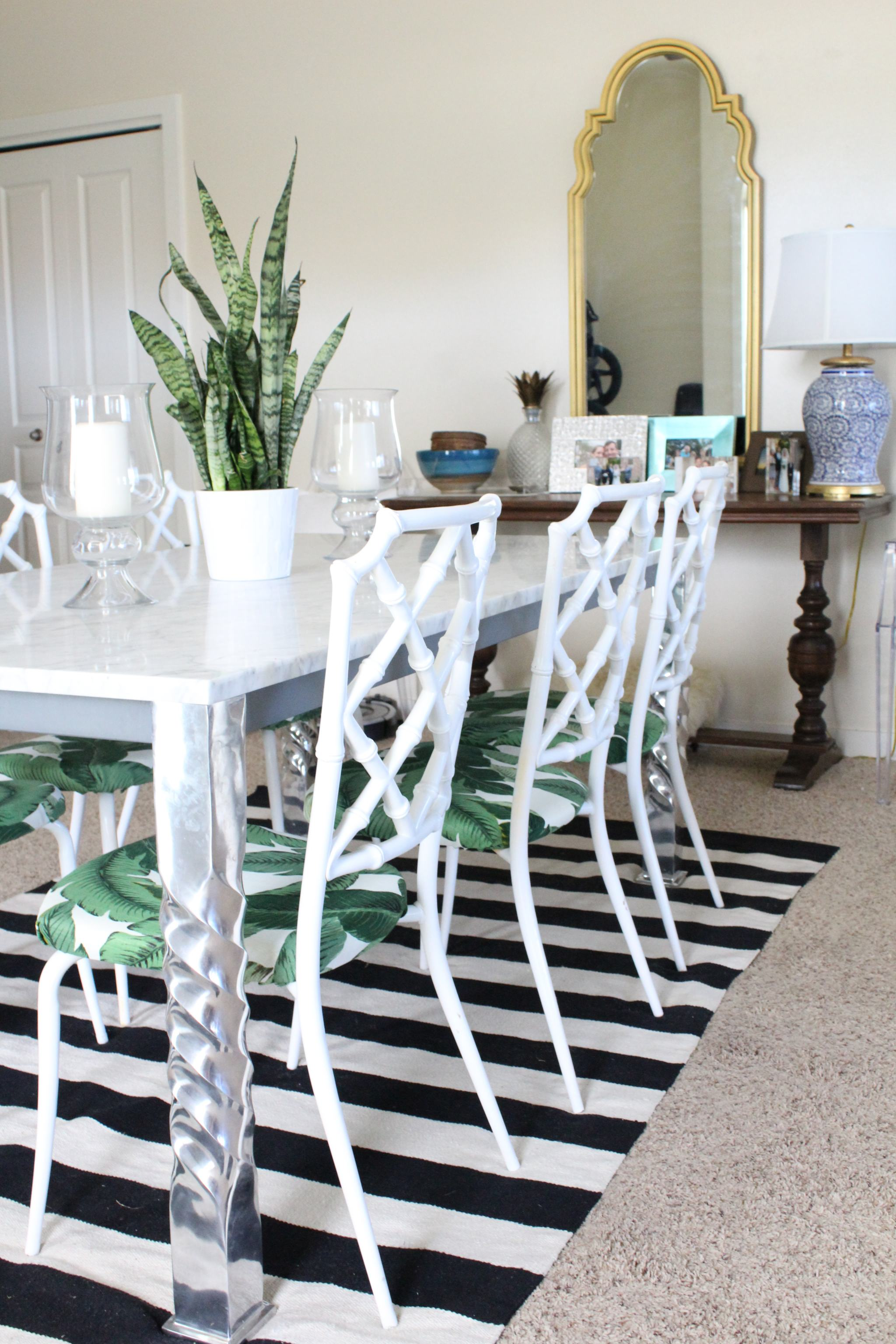 marble dining table - palm leaf fabric - faux bamboo dining chairs - striped rug - queen anne mirror