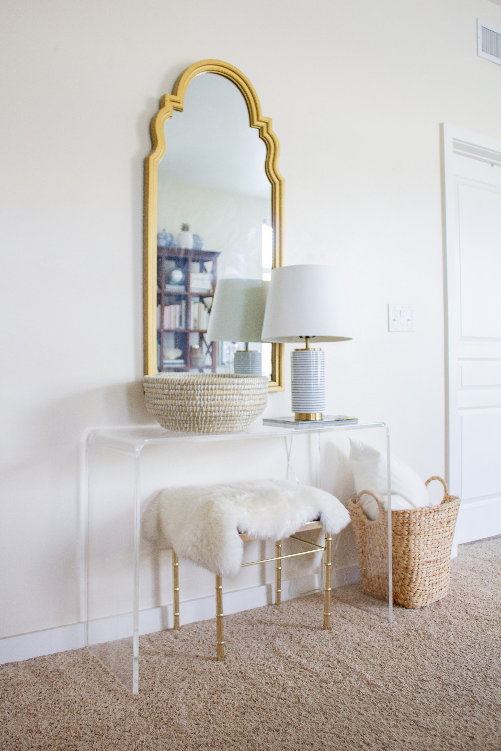 queen anne mirror - acrylic table - peekaboo table - lucite console table - brass faux bamboo stool - blue and white striped lamp - woven bowl basket