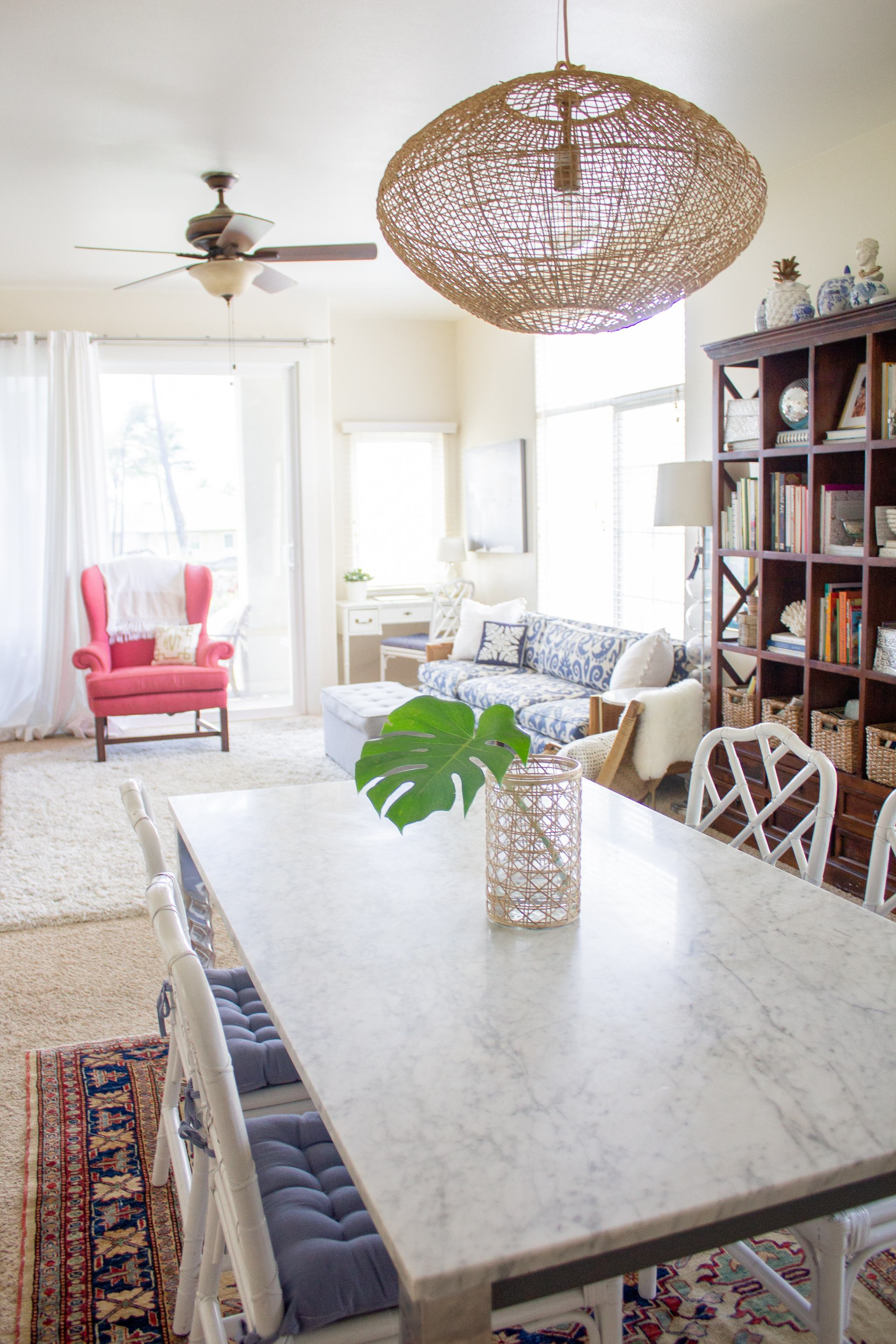 tall bookcase - blue and white ginger jars - how to decorate a bookcase - bookshelf - marble dining table - chinese chippendale chairs - ballard design faux bamboo chairs - woven light fixture - project 62 leanne ford lights - rattan light - rattan lamp - woven lamp - Afghan carpet - oriental rug - crate and barrel marble table - parsons table