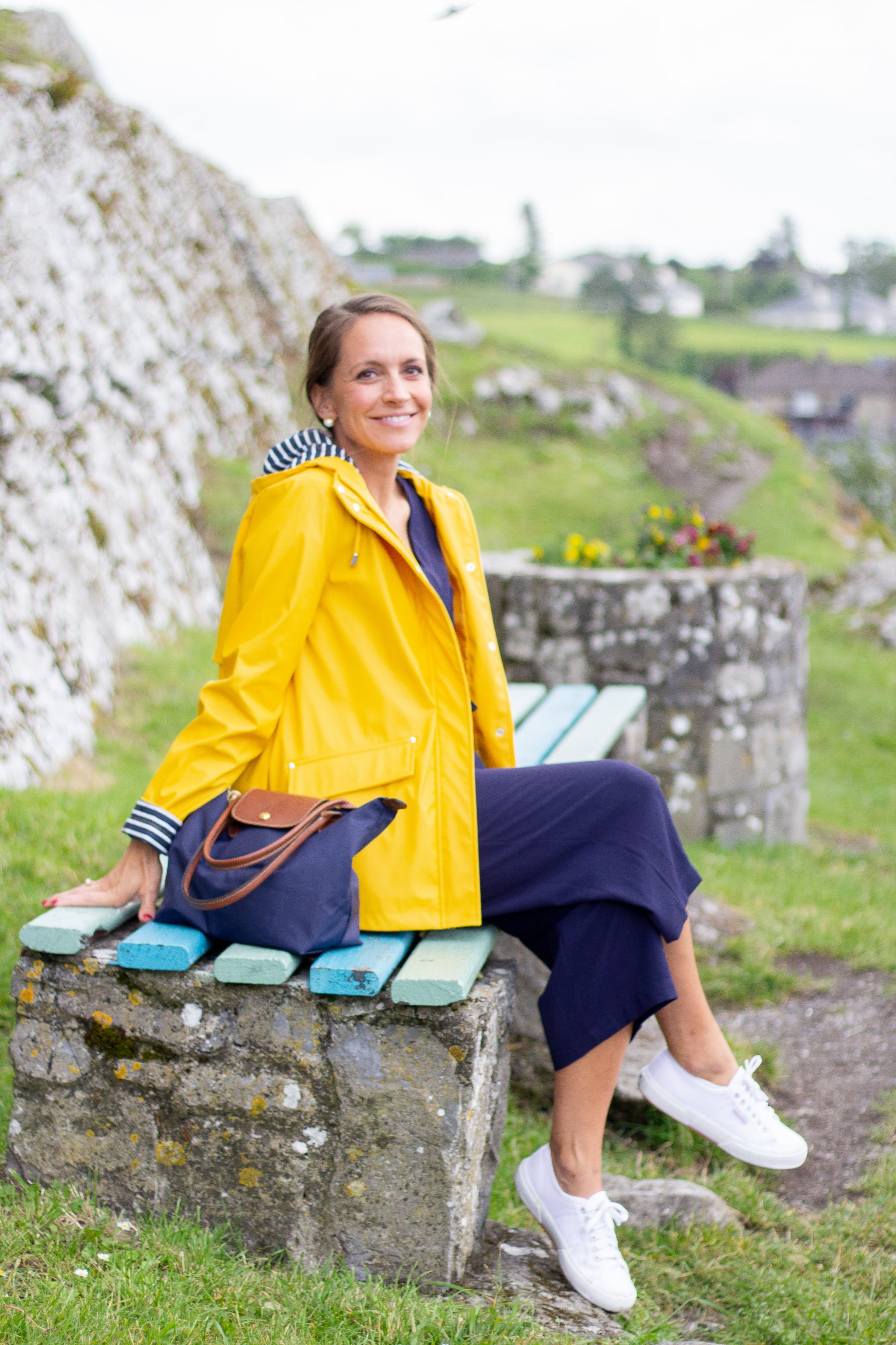 classic style - maternity style - second trimester outfit idea - pregnancy style - jumpsuit and sneakers - superga sneakers - white superga sneakers - superga cotu sneakers - yellow rain jacket - traveling in ireland - rock of cashel - blue and yellow outfit