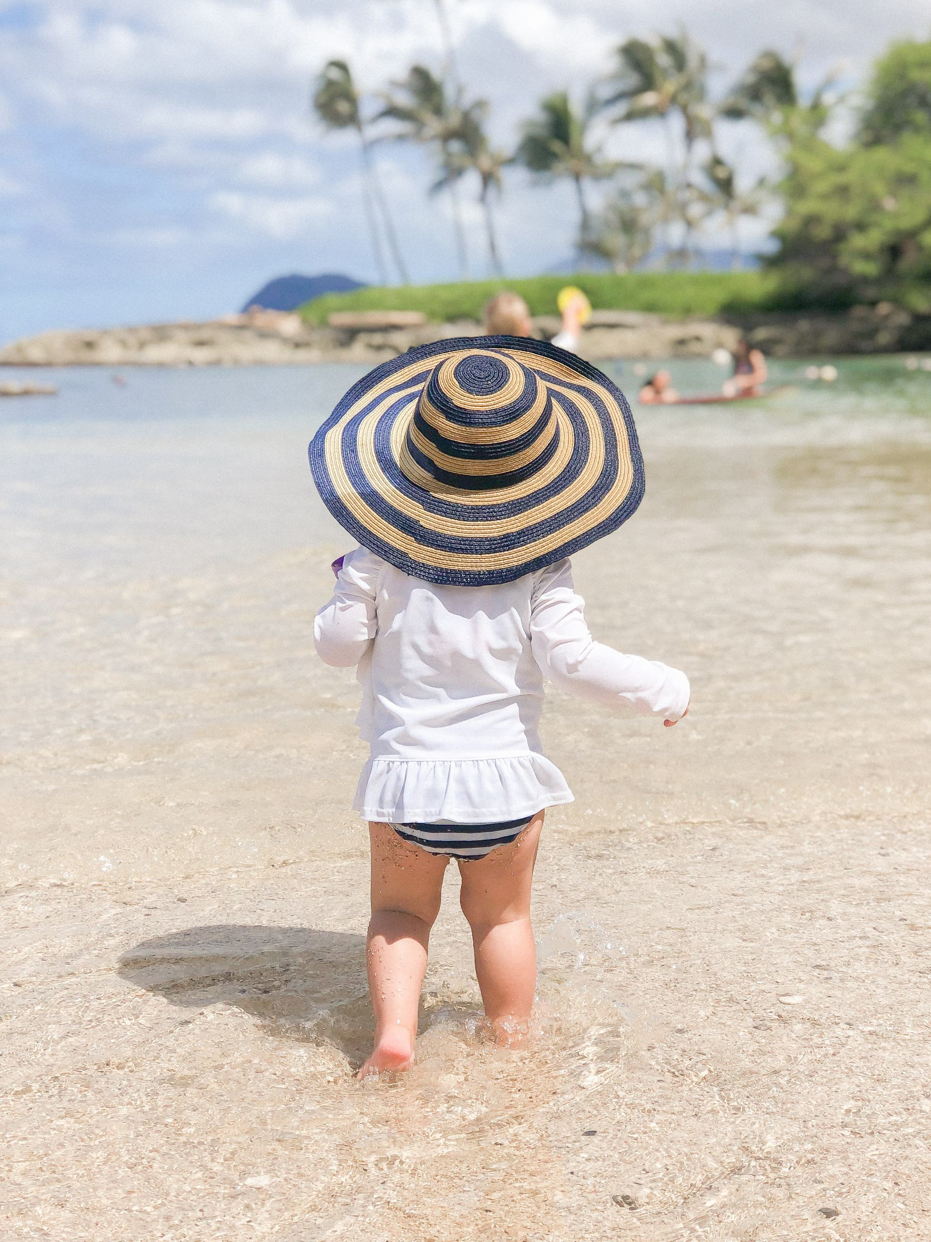 Paradise Cove Lagoon - toddler stripe sun hat - toddler friendly beach - best family beach on Oahu - kid friendly beaches in Hawaii - military family Hawaii - kid friendly activities in Hawaii - kid activities on Oahu - kid activities in Honolulu - toddler friendly Hawaii - Things for toddlers to do in Hawaii