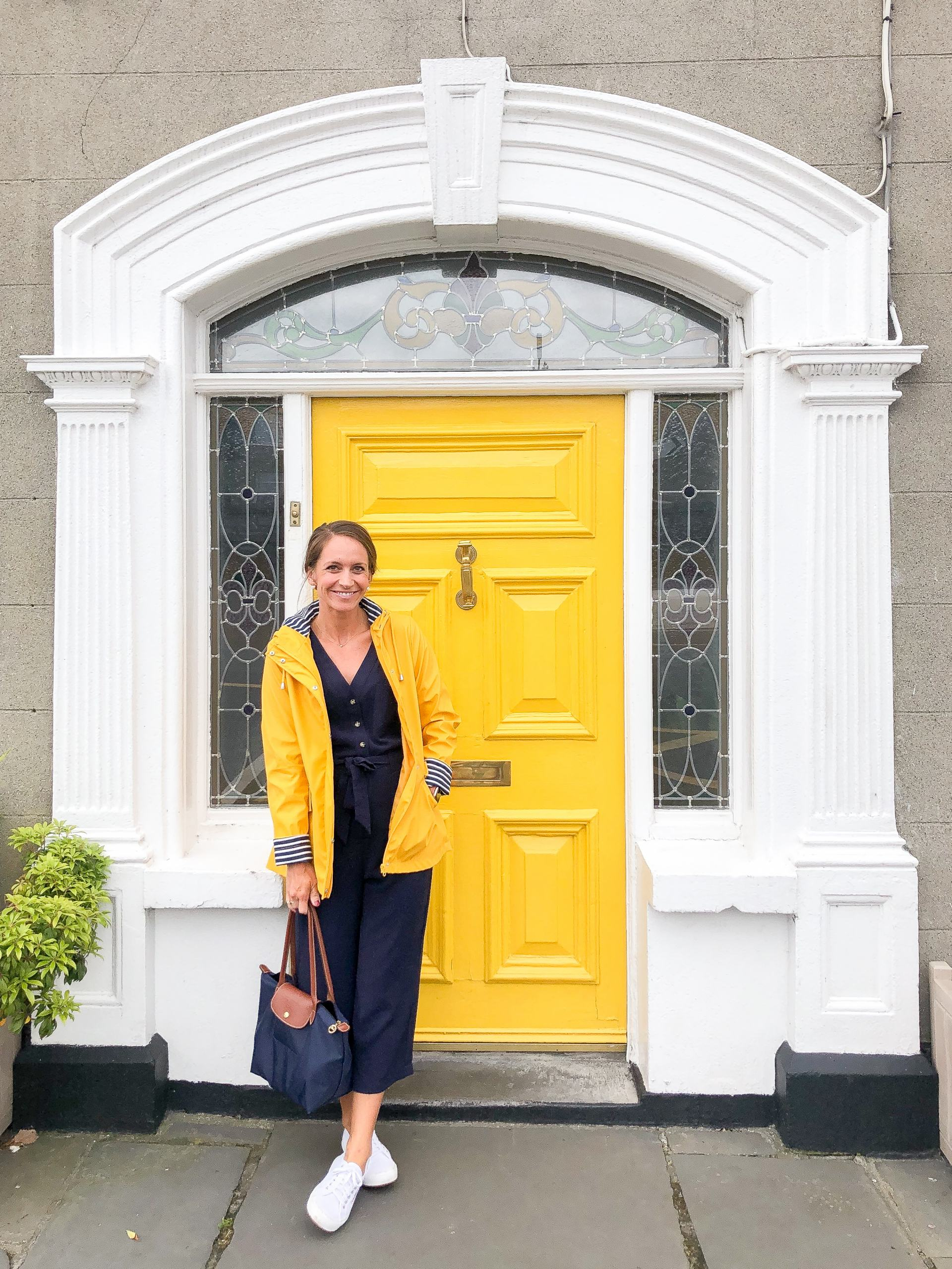 traveling in ireland -doors of ireland - travel style - travel outfit inspo - yellow rain jacket - rock of cashel