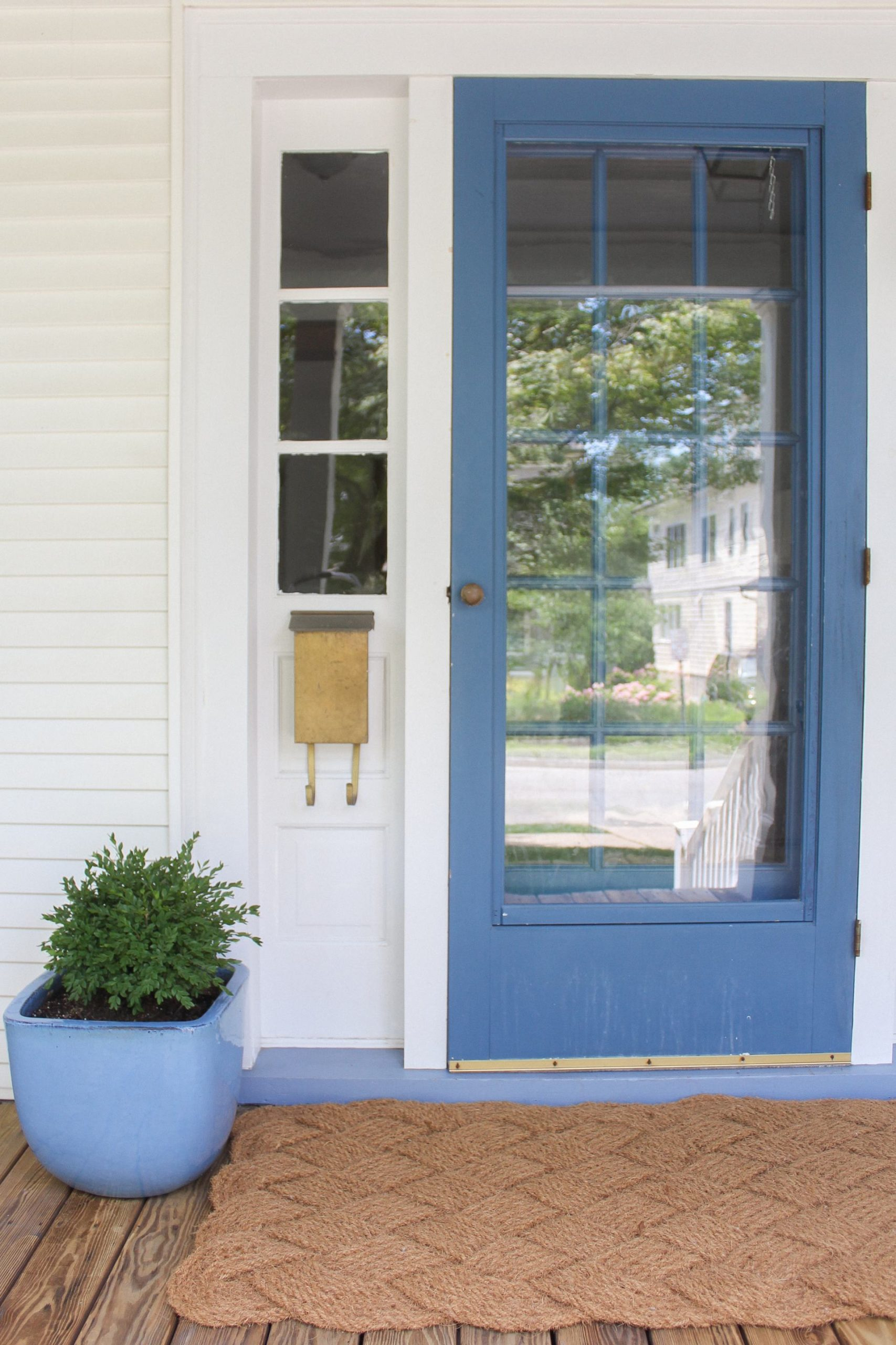 blue front door with brass mailbox and boxwood in blue planter