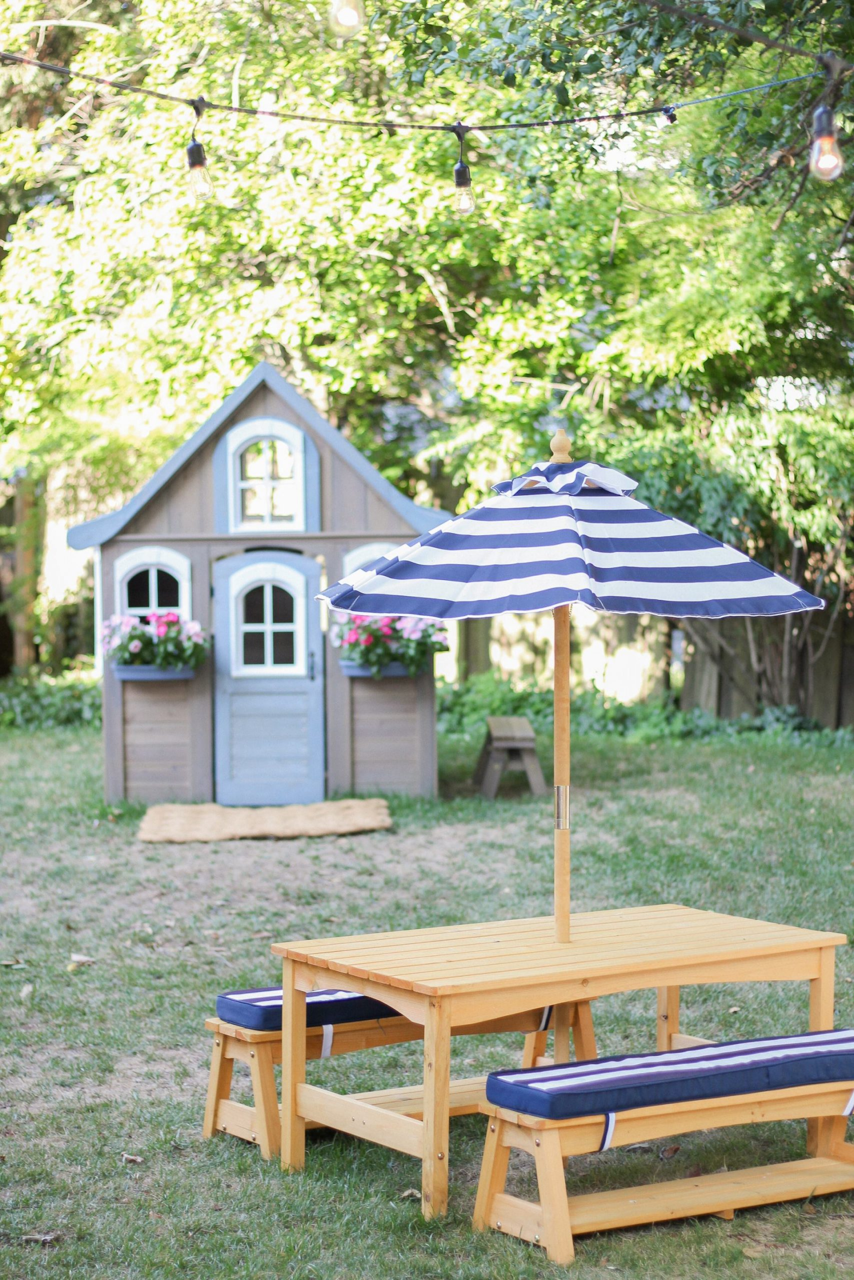 kids picnic table with striped umbrella and cushions and wooden playhouse
