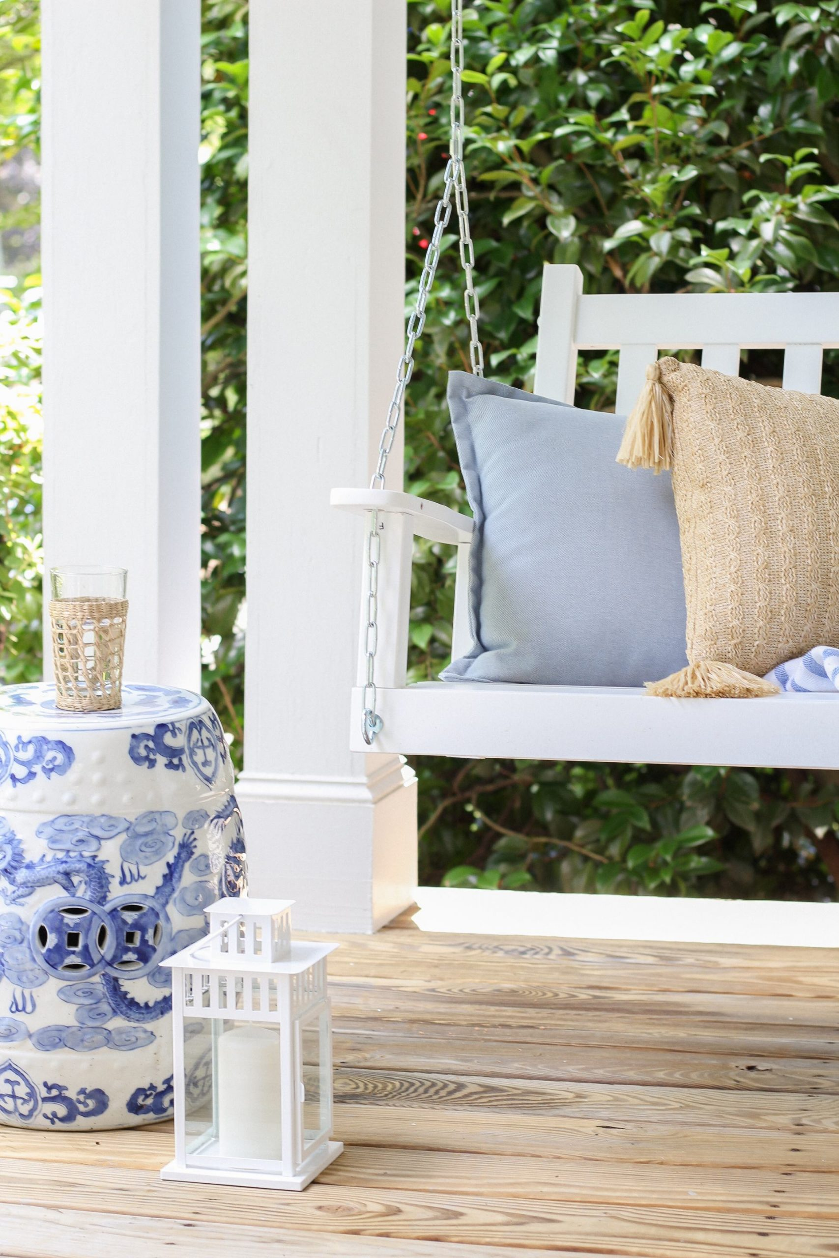 front porch swing with blue pillow and natural pillow and blue and white ginger jar